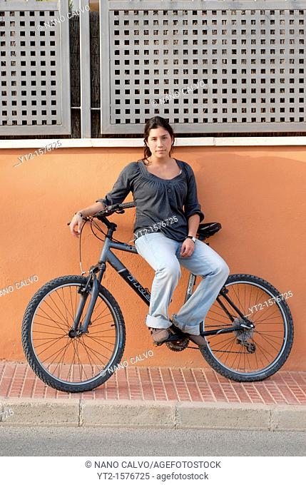Mixed race young woman with her bicycle in Ibiza