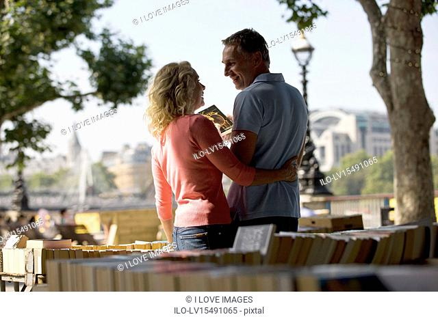 A middle-aged couple looking at books at a book stall