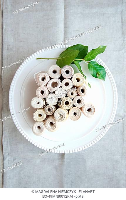 Rolls of fabric and leaf on plate
