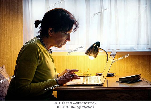 Woman working with a laptop, with glasses and a lighted lamp on the table