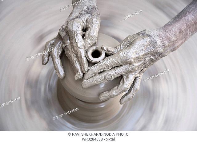 Pottery , artist muddy hands making clay pot giving shape on spinning wheel , semi urban village Dilwara , Udaipur , Rajasthan , India