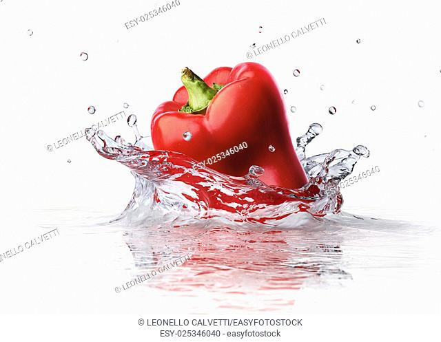 Red sweet bell pepper falling and splashing into clear water