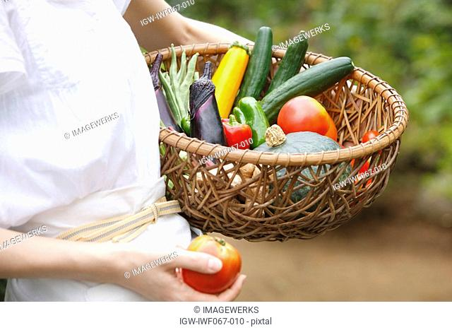 Woman holding vegetables in basket, close-up, mid section
