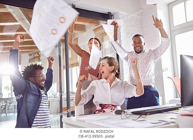 Exuberant business people celebrating, throwing paperwork overhead in office