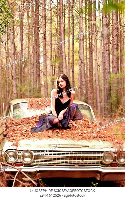 Portrait of a 20 year old brunettte woman sitting on an old car in a forest setting