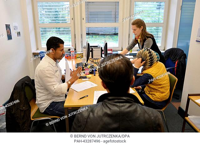 Interpreter Ahmed Yasser (L) and consultant Anna-Maria Appel (R) speak with Syrian saylum seekers in an outpost of the Federal Office for Migration and Refugees...