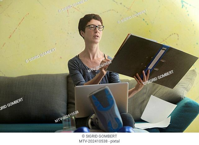 Woman with broken leg working on laptop and reading document