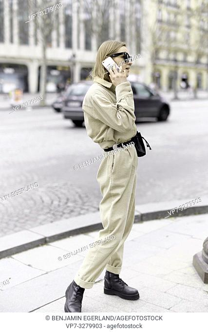 fashionable woman calling with mobile phone at street during fashion week, in Paris, France