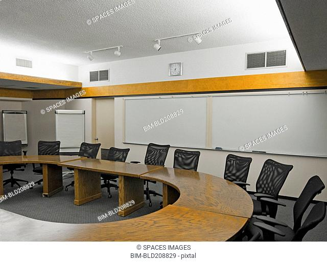 A boardroom with an oval table and chairs