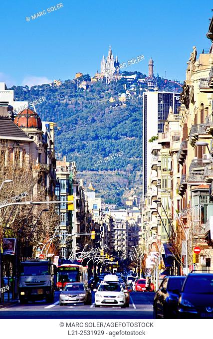 Urban view of the city in a sunny day, blue sky. Tibidabo and Collserola Sierra from Balmes street. Barcelona, Catalonia, Spain