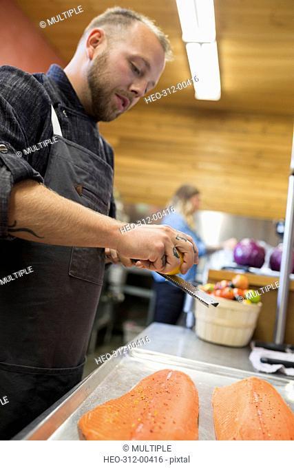 Chef grating lemon over fresh salmon in restaurant commercial kitchen