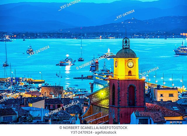 Europe, France, Var, Saint-Tropez. The parochial church in the village and the Gulf of Saint-Tropez by night
