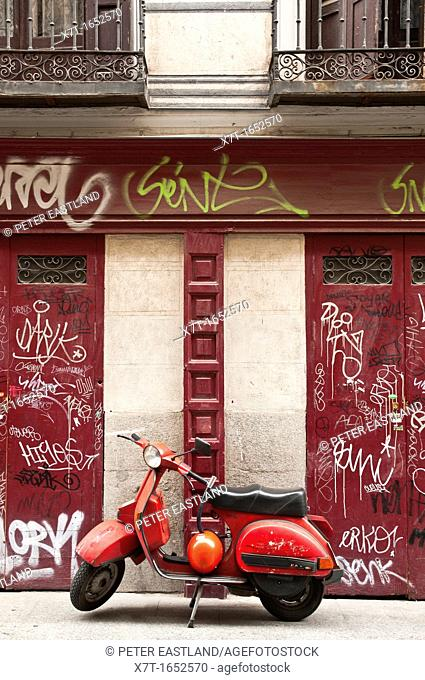 Red scooter and graffiti covered shutters central, Madrid, Spain