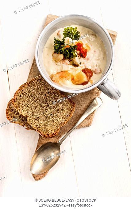 irish seafood chowder in a mug with soda bread and spoon on wooden board