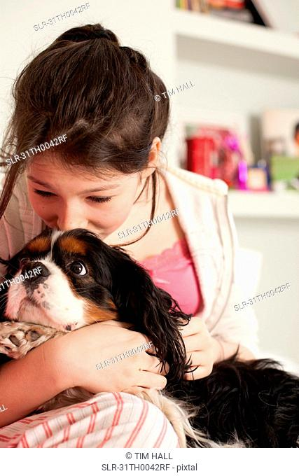 teenage girls playing with dog at home