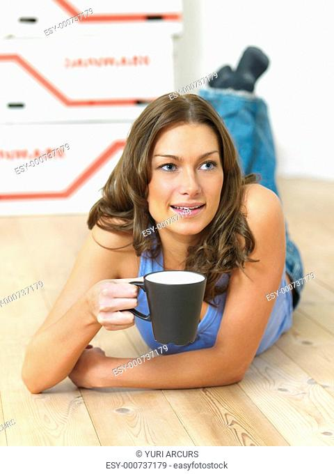 Young woman lying on her stomach, holding coffee cup in an empty house