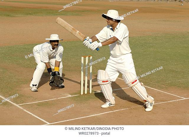 Indian right handed batsman in action playing square cut shot in cricket match MR705L