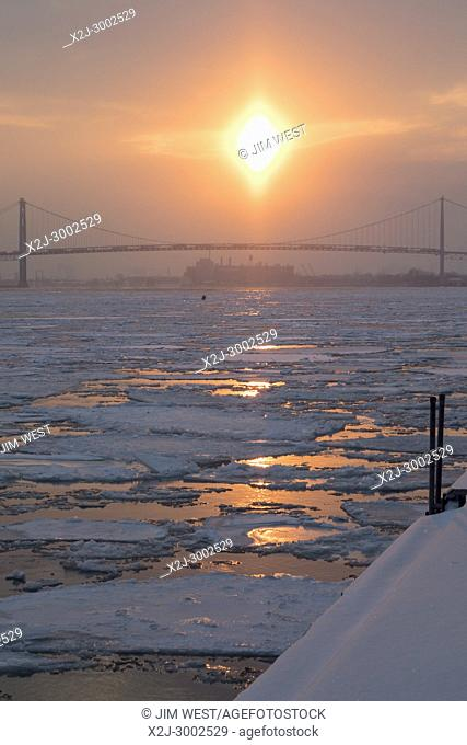 Detroit, Michigan - Ice clogs the Detroit River as the sun sets beyond the Ambassador Bridge. Frigid temperatures continue in the midwest