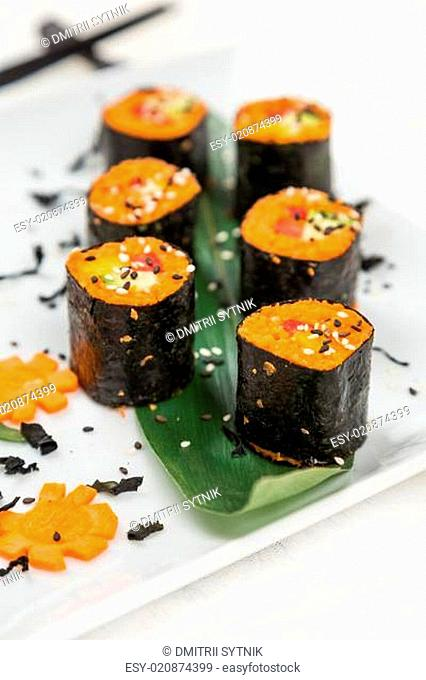 serving raw vegetarian rolls with carrot