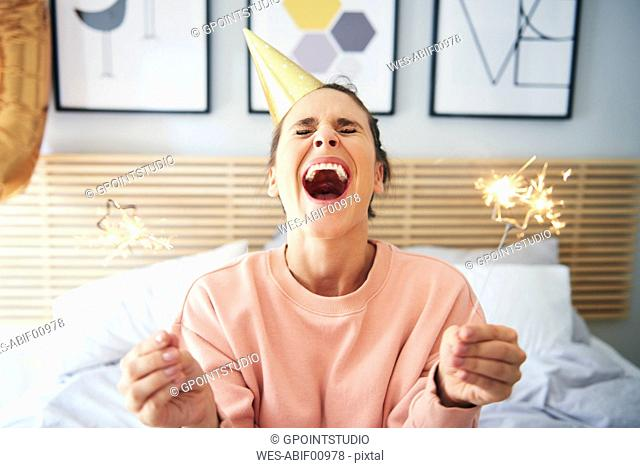 Cheerful woman during her birthday with sparklers