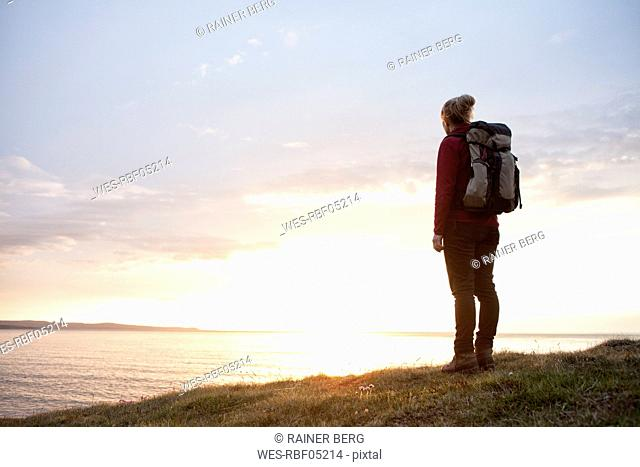 Iceland, back view of hiker looking at view by twilight