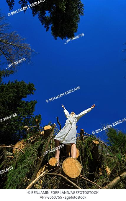 Low angle view of woman in nature wearing a white bathrobe. Waakirchen, Bavaria, Germany