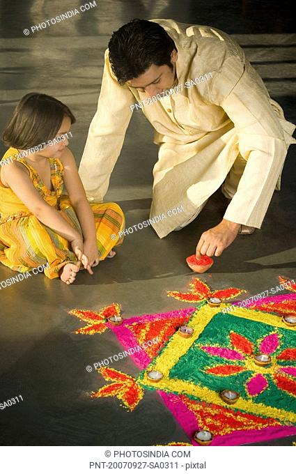 Mid adult man making a rangoli with his daughter