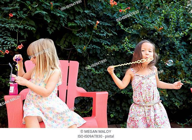 Girls blowing bubbles in garden