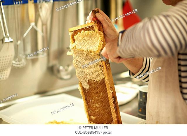 Cropped image of female beekeeper scraping honeycomb in kitchen