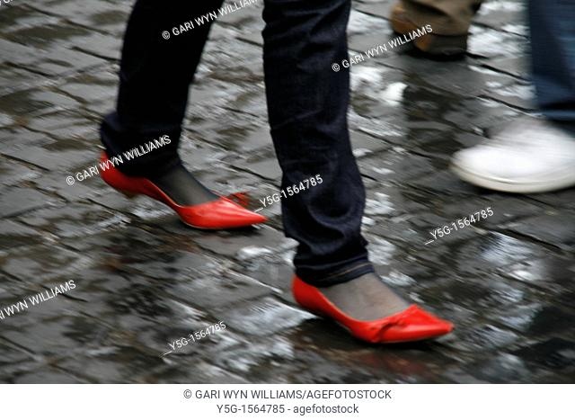 woman wearing red shoes walking in town