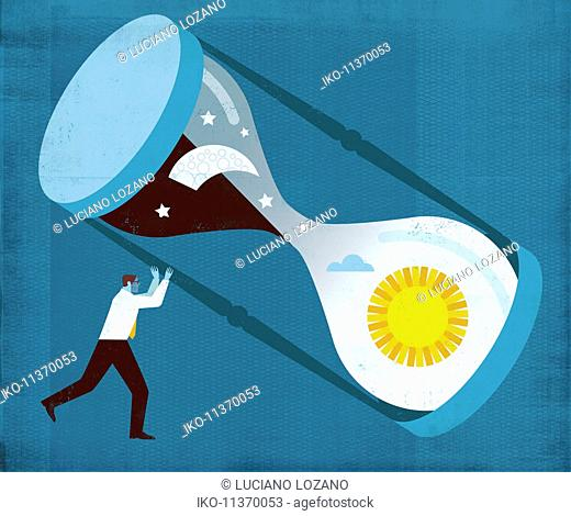 Businessman turning hourglass with sun and moon