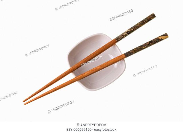 Two wooden chopsticks on white saucer. Sticks are decorated with temple theme ornamentation. Isolated on white