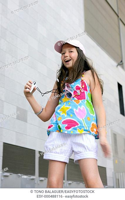 Brunette teen little girl dancing mp3 headphones music in the city