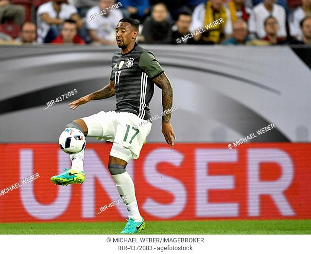 Jerome Boateng, German football player, playing the ball in front of adboard OUR, WWK Arena, Augsburg, Bavaria, Germany