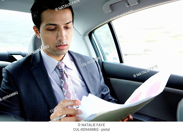 Businessman in back seat of car reading document