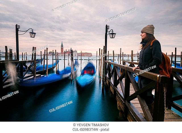 Woman on pier by gondolas in Grand Canal, San Giorgio Maggiore Island in background, Venice, Italy