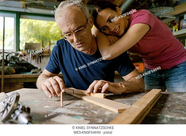 Mature woman watching man working in workshop
