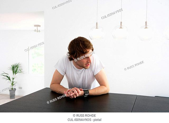 Pensive young man sitting at dining room table