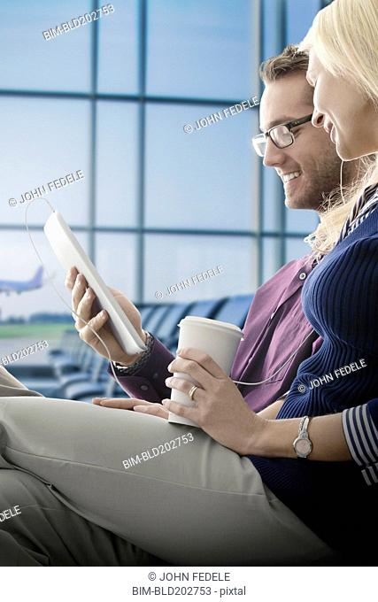 Caucasian couple using digital tablet in airport