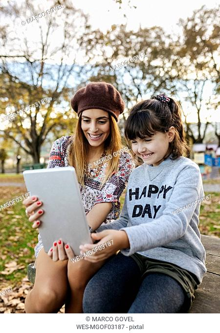 Mother and little daughter taking selfie with tablet in autumnal park