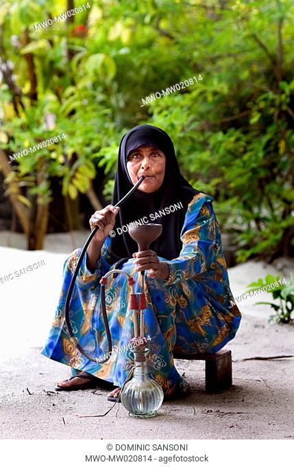 A woman smoking tobacco with a water pipe The Island of Utheem in North Maldives September 8, 2006