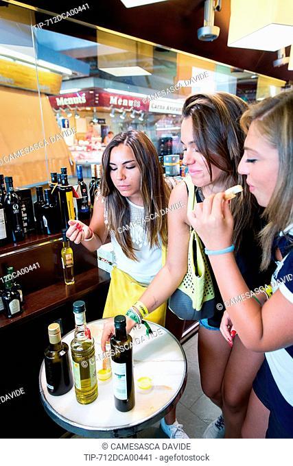 Spain, Catalonia, Barcelona, Santa Caterina market, Tourists tasting diffirent types of olive oil
