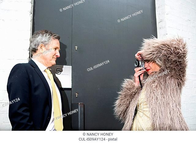Couple dressed up and taking photograph in front of door