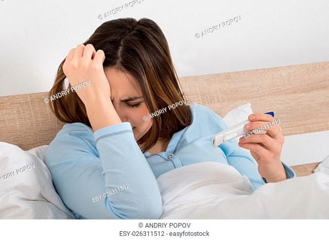 Unhappy Young Woman Checking Pregnancy Test On Bed