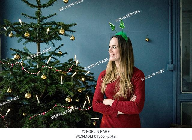 Content woman with Christmas headdress standing besides decorated Christmas tree