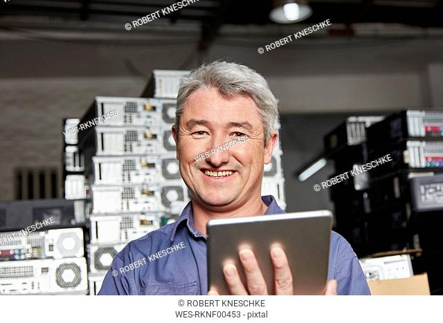 Worker in computer recycling plant using digital tablet