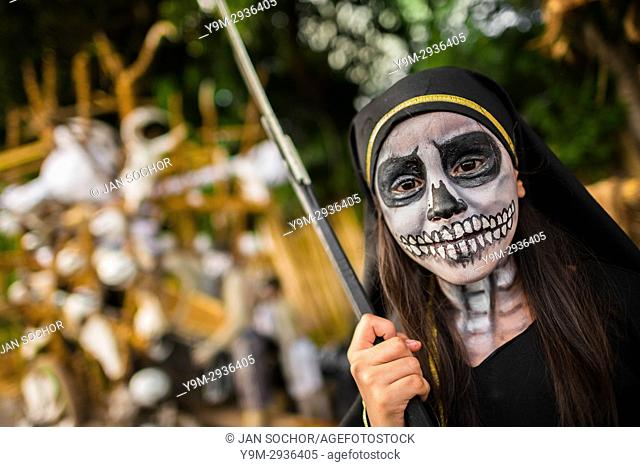 A Salvadoran girl with skull face paint performs in the La Calabiuza parade at the Day of the Dead festivity in Tonacatepeque, El Salvador, 1 November 2016