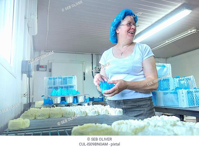 Female cheesemaker looking back while preparing cheeses