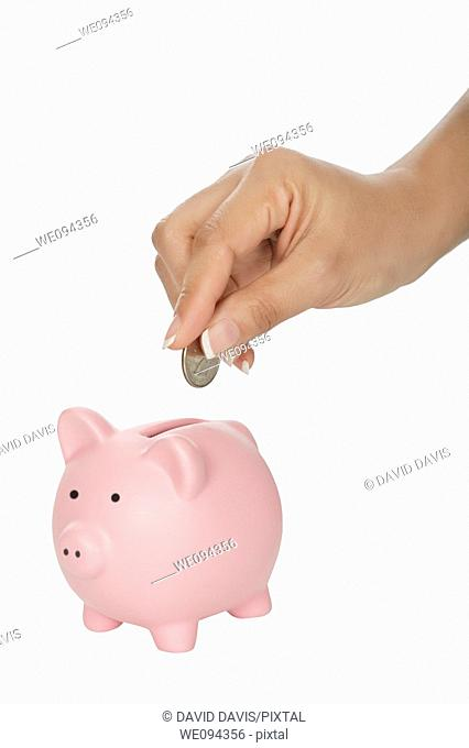 Woman placing a quarter into a piggy bank isolated on a white background