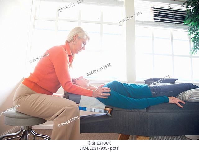 Caucasian chiropractor massaging shoulders of client